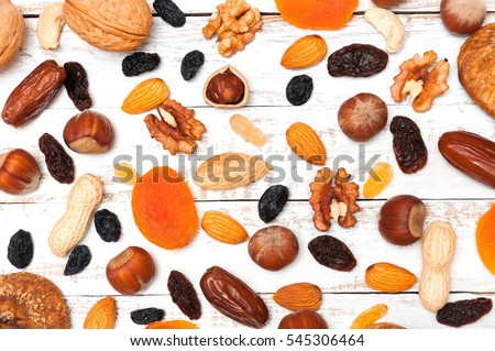 Mix of dried fruits and nuts on a white background  wooden boards . Top view. Symbols of judaic holiday Tu Bishvat. Thanksgiving Day.