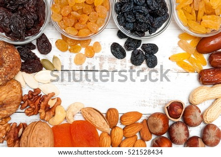 Mix of dried fruits and nuts on a white vintage wood background with copy space. Top view. Symbols of judaic holiday Tu Bishvat.