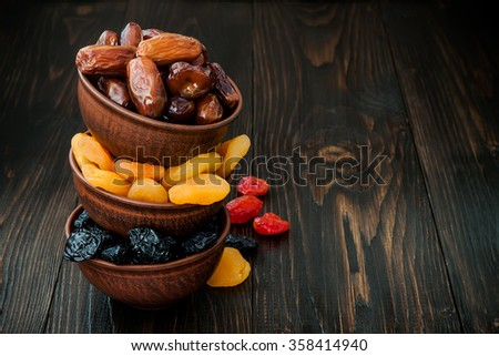 Mix of dried fruits and nuts on dark wood background with copy space. Symbols of judaic holiday Tu Bishvat - stock photo