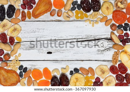 Mix of dried fruits and nuts on white wooden table - symbols of judaic holiday Tu Bishvat. Copyspace background.Top view. - stock photo
