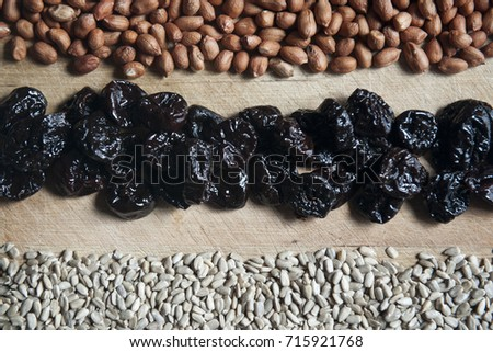 Mix of dried fruits on wooden background, plums sunflower seeds and peanuts