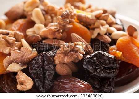 Mix of dried fruits with nuts closeup macro shot, selective focus