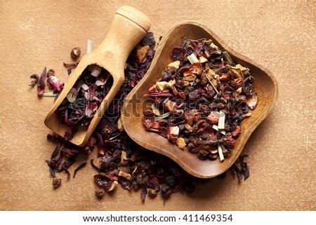 Mix of dried tea leaves in bowl and scoop on paper background - stock photo