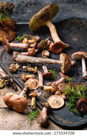 Mix of forest mushrooms on black cutting board over old wooden table. See series - stock photo
