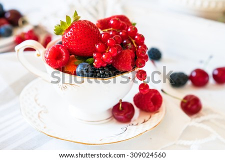 Mix of fresh berries in a cup of tea - stock photo