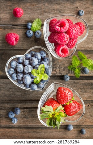 Mix of fresh berries in a glass ramekins in shape of heart, on wooden background, top view  - stock photo