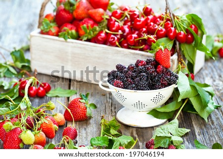 Mix of fresh berries on rustic wooden background. Also available in vertical format.  - stock photo
