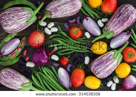 Mix of fresh farmers market vegetable from above on the old wooden board. Healthy eating background. Top view  - stock photo