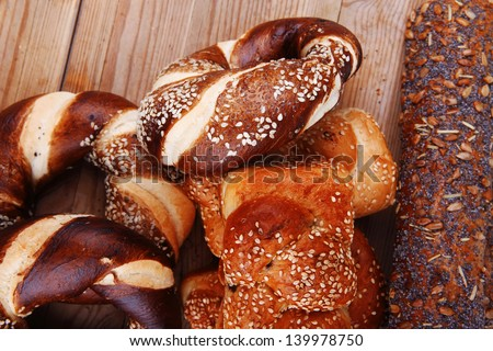 mix of fresh homemade baguettes , pretzels and wheat loafs, on wooden table