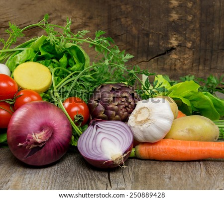 mix of fresh raw vegetables on old wooden table - stock photo