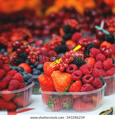 Mix of fresh ripe berries raspberry, strawberry, blackberry and blueberry in plastic boxes with disposable fork in market. Square image with selective focus - stock photo