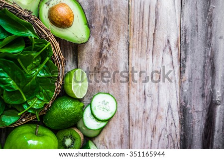 Mix of green fruits and vegetables on rustic wooden background - stock photo
