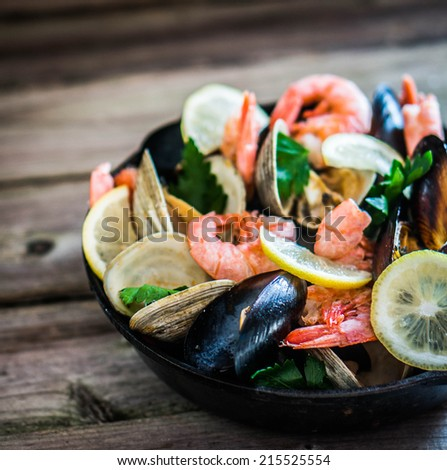 Mix of mussels,clams and shrimps on wooden background - stock photo