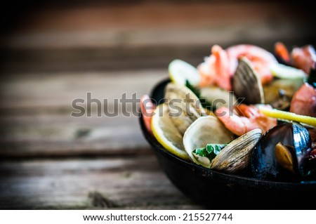 Mix of mussels,clams and shrimps on wooden background