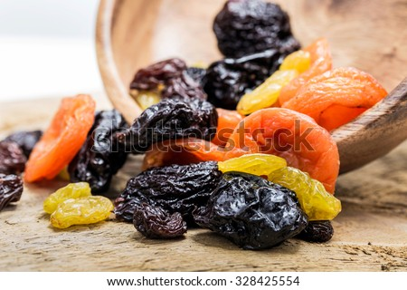 Mix of of dried fruits on a wooden background. - stock photo