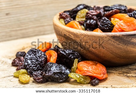 Mix of of dried fruits on a wooden background.