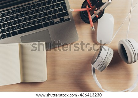 Mix of office supplies and gadgets on a wooden table background.