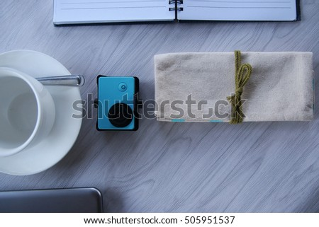 Mix of office supplies and gadgets on a wooden table background