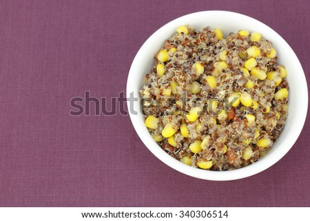 Mix of organic red quinoa cooked with yellow corn and red tomato in a white bowl on a purple cloth placemat. Vegetarian recipe of red quinoa, corn and diced tomatoes.