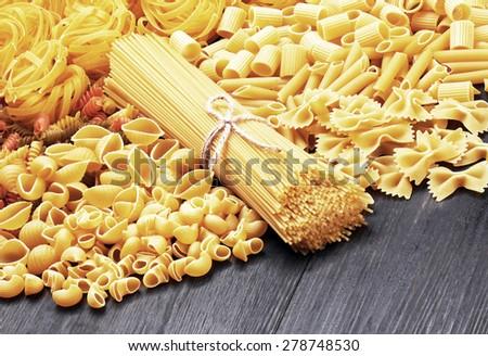 Mix of pasta on wood background - stock photo