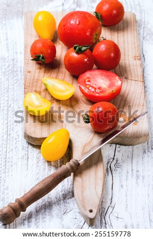 Mix of red and yellow cherry tomatoes on cutting board and vintage knife over white wooden table. See series.  - stock photo