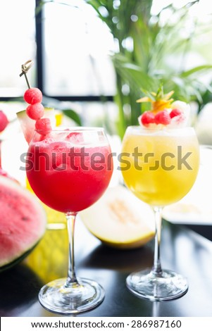 mix of refreshing glass of bright juicy melon and watermalon smoothie or lemonade with ice on a table at a restaurant with the decor of the bright dishes and pieces of melon - stock photo
