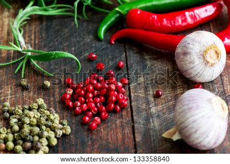 Mix of spices, herbs and vegetables on wood table - stock photo