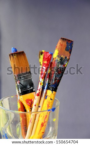 Mix of vivid paintbrushes stained with paints  - stock photo