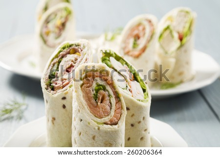 Mix of wraps with ham, chicken, salmon and crab served on a plate - stock photo