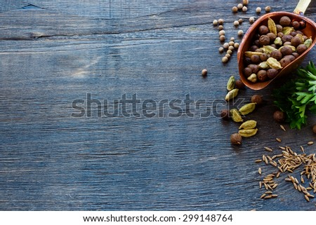 Mix pepper in vintage scoop, herbs and spices over dark wooden background with space for text. Cooking ingredients. - stock photo