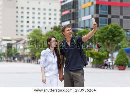 Mix race couple tourists taking selfie photo picture smile, asian girl and caucasian man city street - stock photo