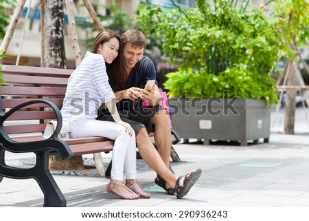Mix race couple using cell smart phone sitting in bench smile, asian girl and caucasian man city street