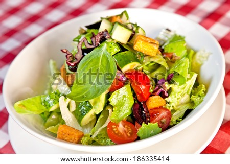 Mix salad with lettuce, cherry tomatoes, cucumber, croutons, basil and mint