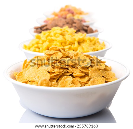Mix variety of breakfast cereal in white bowls over white background - stock photo
