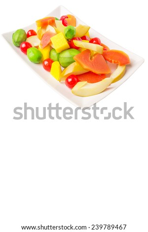 Mix variety of pickled fruit of papaya, mango, cherry and jicama on a white plate