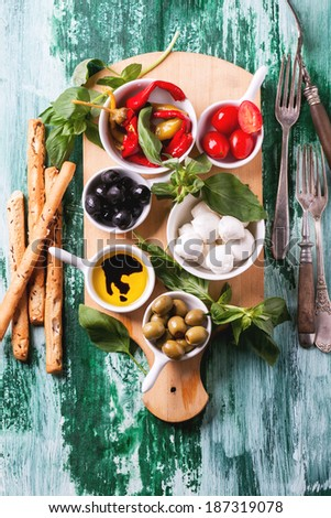 Mixed antipasti olives and mozzarella served on wooden cutting board over green wooden table with vintage fork. Top view. - stock photo