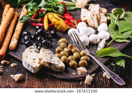 Mixed antipasti pickled blue cheese, olives and mozzarella served on cast-iron board over wooden table with vintage fork. - stock photo