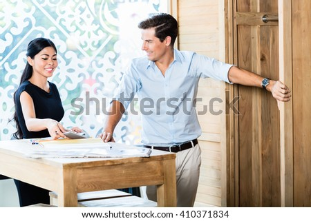 Mixed Asian Caucasian couple in furniture store or showroom calculating price, she is showing calculator to him - stock photo