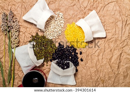 Mixed beans in sack on brown paper background, mung bean,soybean, black bean ,green bean,millet - stock photo