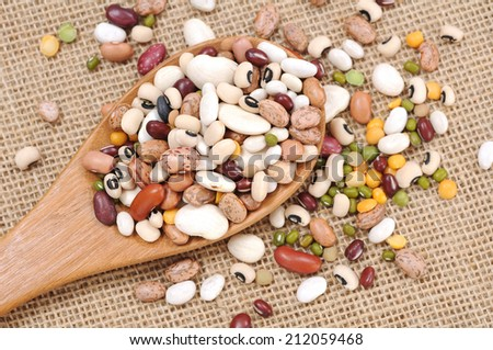 mixed beans with wooden spoon on table - stock photo