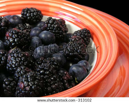 mixed blueberries and blackberries in a bowl on a plate on a black placemat, with cup faded in background
