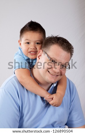 Mixed boy of East Asian and Caucasian and his father, the boy is hugging his father's neck and both are smiling with pleasure and joy