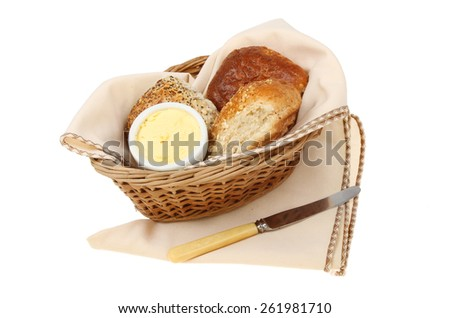 Mixed bread rolls in a basket with butter serviettes and a knife isolated against white - stock photo