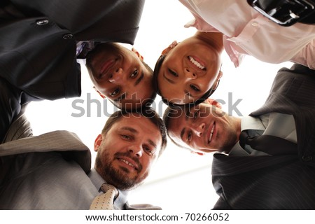 Mixed businessteam with heads together over white - stock photo