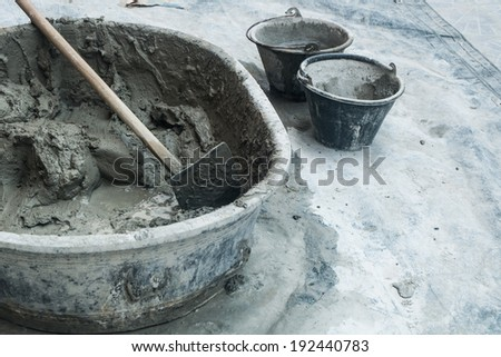 mixed cement in the container with the tool prepared for building