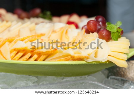 mixed cheese plate with grapes and herbs at a buffet