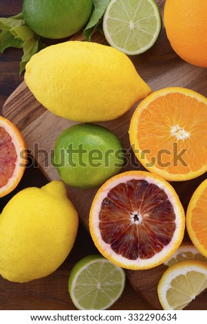 Mixed citrus fruit including navel and blood oranges, lemons and limes on dark wood table. - stock photo