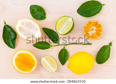 Mixed citruses fruit oranges, lemon and lime on wooden background with orange leaf. - stock photo