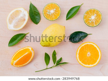 Mixed citruses fruit oranges, lemon on wooden background with orange leaf. - stock photo
