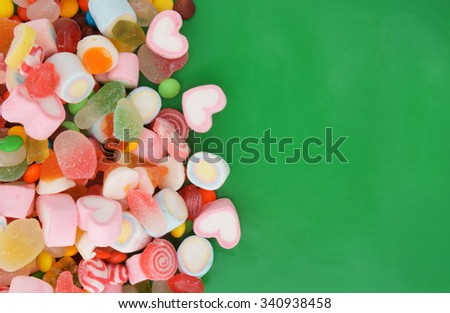 Mixed colorful fruit candies and jellies on green background with room for text - stock photo